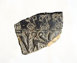 Figure 4. Image of a lotus motif from the Poggio Civitate collection. Three partial and one full lotus palmette are visible in the upper register of the pottery fragment. (Tuck 2012)